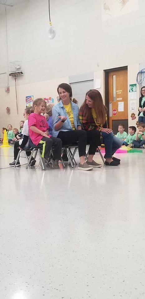 students and teacher playing musical chairs