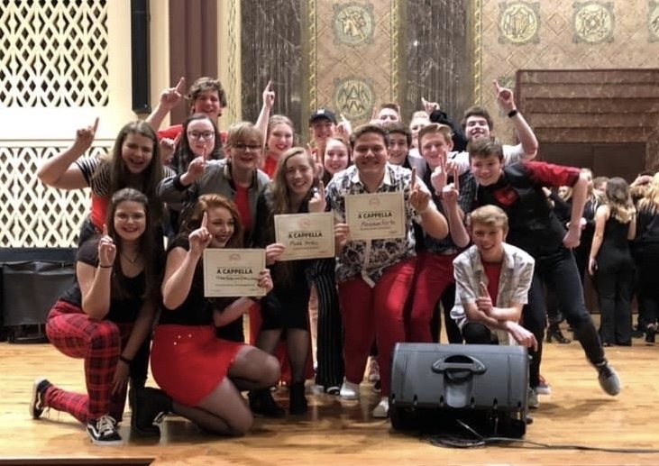 Maximum Forte members holding up number 1 fingers and the certificates they earned for first place, best solo, and best choreography.