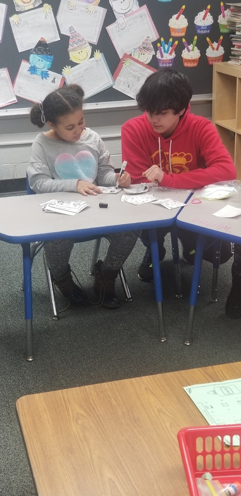 8th grade student helping a kindergarten student on her math
