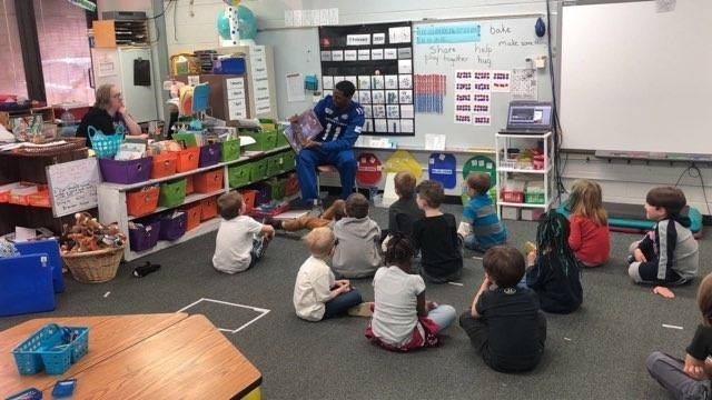 EIU fball player reading to students