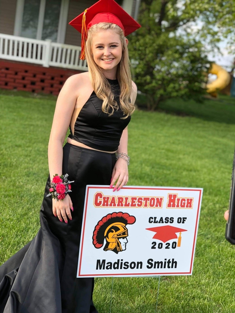 Senior in prom dress and mortar board standing with yard sign